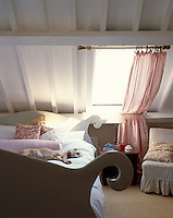 A pretty and intimate bedroom under the eaves is designed in the Swedish style