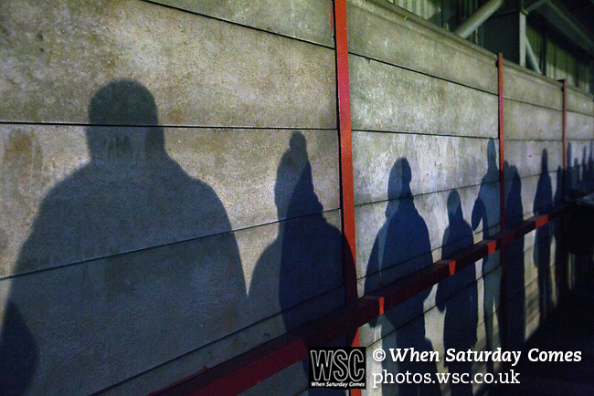 Witton Albion 1 Warrington Town 2, 26/12/2017. Wincham Park, Northern Premier League. Silhouettes of spectators in the shed watching the second half action at Wincham Park, home of Witton Albion (in red) during their Northern Premier League premier division fixture with Warrington Town. Formed in 1887, the home team have played at their current ground since 1989 having relocated from the Central Ground in Northwich. With both team chasing play-off spots, the visitors emerged with a 2-1 victory, the winner being scored by Tony Gray in second half injury time, watched by a crowd of 503. Photo by Colin McPherson.