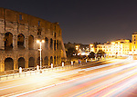 The lights of passing traffic lights the ancient Roman Colosseum at night.