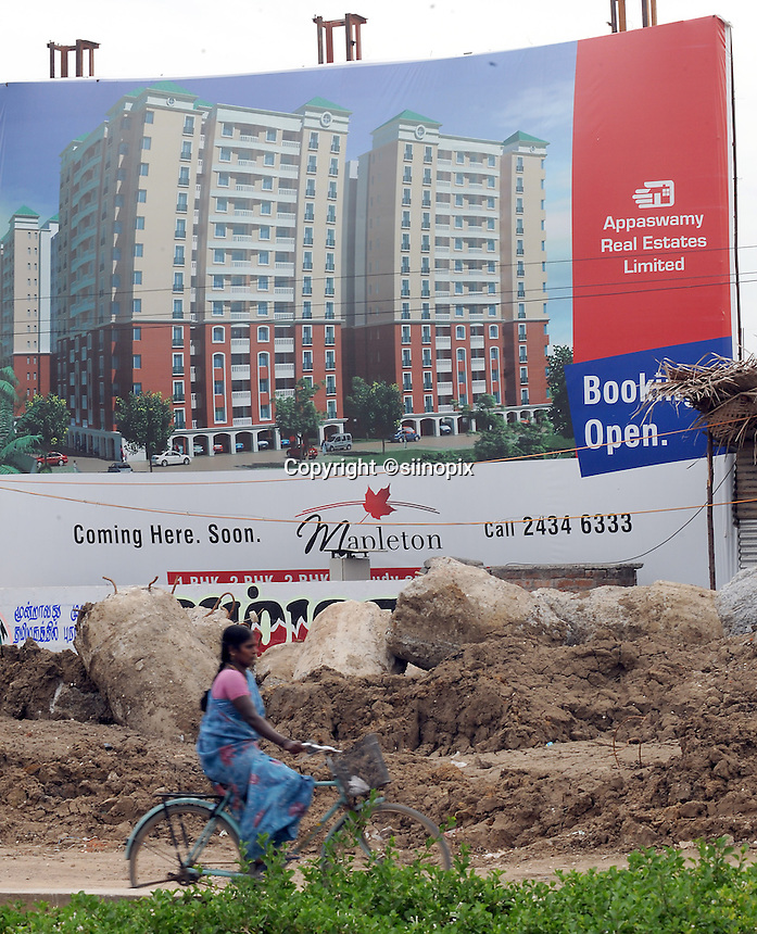 A lady on bicycle is passing in front of new high rise apartment blocks in Madras, Inidia