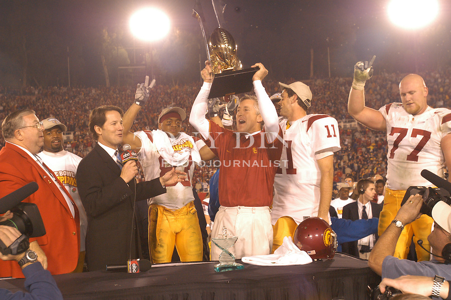 Trojans head coach Pete Carrol hoists the Rose Bowl Championship Trophy after the Wolverines' 14-28 loss to USC on Thursday, January 1, 2004 at the Rose Bowl in Pasadena, California. It was Michigan's 18th appearance at the Rose Bowl and the 90th game the bowl has played. (TONY DING/The Michigan Daily)