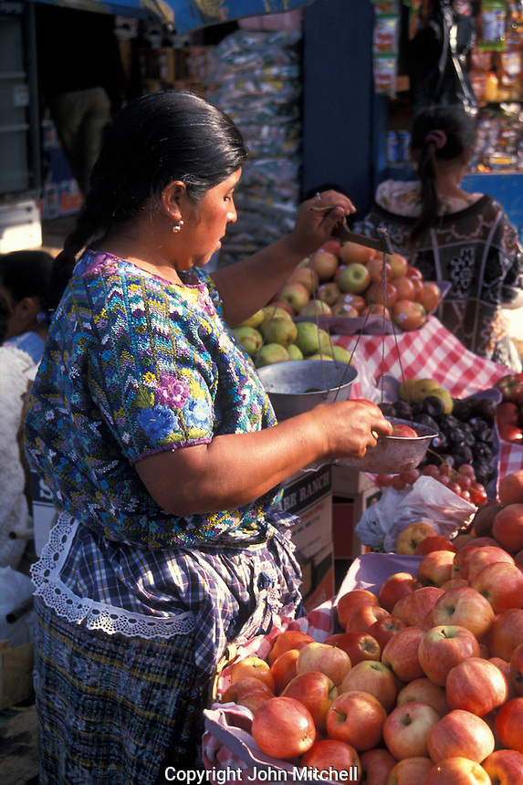 Maya woman weighing apples in the market in Quetzaltenango, Guatemala
