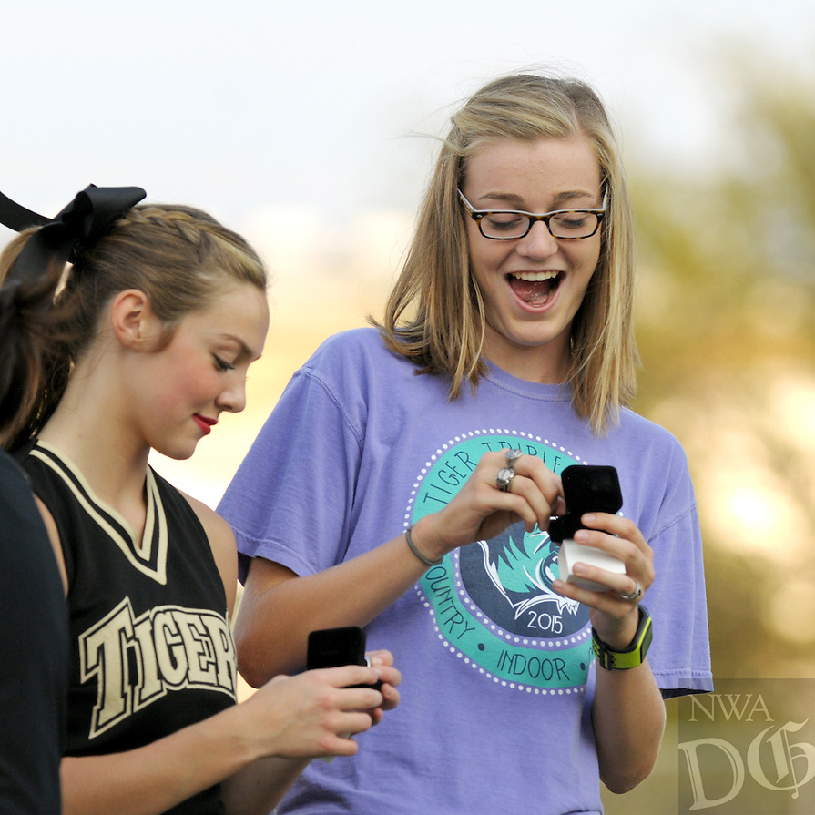 NWA Democrat-Gazette/BEN GOFF @NWABENGOFF<br /> Baylee Barganier (left) and Katie Andrews check out their hardware on Saturday Aug. 22, 2015 during a ring ceremony for last year's 7A state champion track and field team at Tiger Pride night in Bentonville's Tiger Stadium.