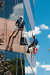 Workers repair weatherproofing on office building in Wakefield, MA while suspended on ropes from the top of the building