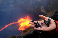 Hawaii, USAan woman holding freshly spattered lava, also known as Peles tears, at the East pond vent, Puu Oo vent, Kilauea volcano, Hawaii, USA Volcanoes National Park, The Big Island of Hawaii, USA
