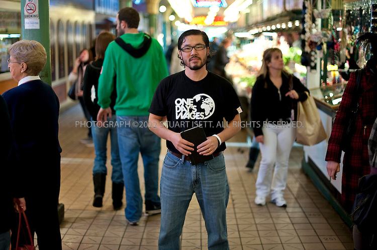 11/4/2009-Seattle, WA, USA...Eugene Cho, 39, is the co-founder and executive director of One Day's Wages, an international grassroots movement dedicated to ending global poverty. The group hopes to get people around the world to donate one day's wages and to renew that donation weekly, monthly, or yearly on their birthdays to the cause of ending extreme global poverty. http://www.onedayswages.org..Here Cho poses at Seattle Pikes Place Market...©2009 Stuart Isett. All rights reserved.