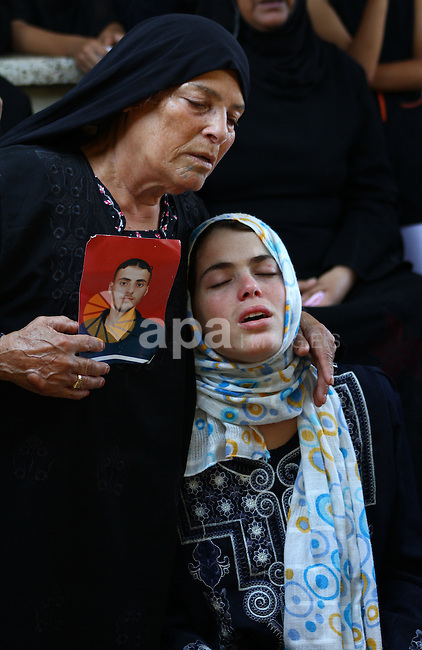 The sister of Palestinian Islamic Jihad militant Anwar Isleem (seens on the photograph) and her mother mourn during his funeral in Bureij Refugee Camp in central Gaza Strip on August 20, 2011. Anwar Isleem and Emad Abu Aabdeh were killed during an Israeli airstrike in response to militant rockets. Photo by Ashraf Amra