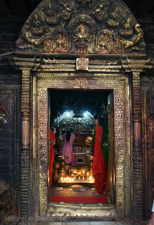 gate of a small temple  in Kathmandu, Nepal, on the way from Thamel to Durbar Square, showing golden metal craftswork, relief, incarnation of Durga. Inside a woman worshipper in pink Sari, candle light burning with holy, purified butter.