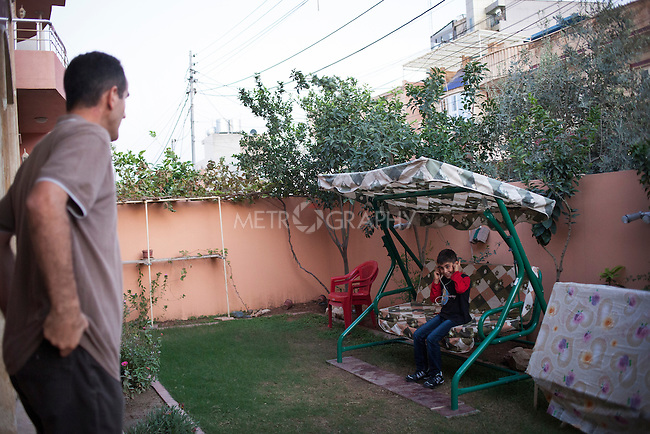 21/10/14. Erbil, Iraq. Salam asks his nephew Milad if he is enjoying the music he is listening to in the garden of their house in Ainkawa, Erbil.