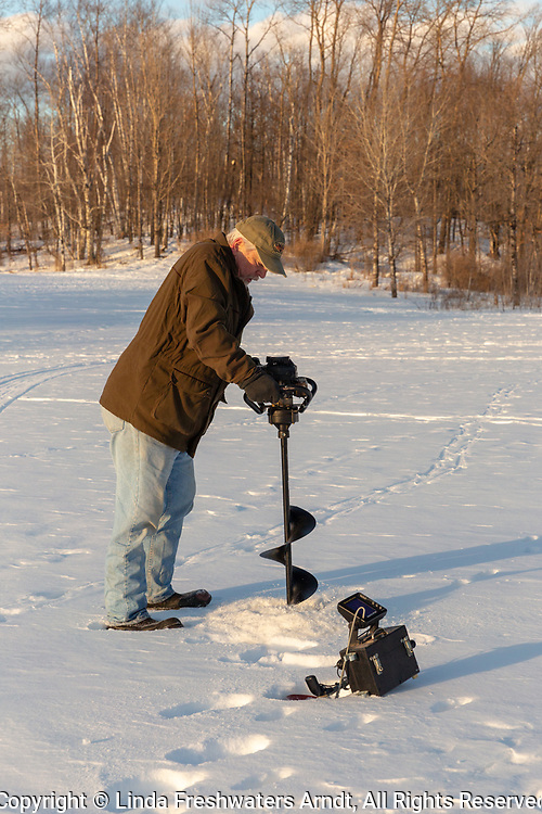 Fisherman using an ice auger to drill a hole in the ice.