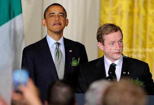 Irish Prime Minister Enda Kenny (R) makes remarks as United States President Barack Obama listens during a reception in the East Room of the White House, March 20, 2012, in Washington, DC. The two leaders concluded a working day devoted to discussions on economic matters, Ireland's peace keeping participations and foreign policy issues like Syria and Iran.  .Credit: Mike Theiler / Pool via CNP
