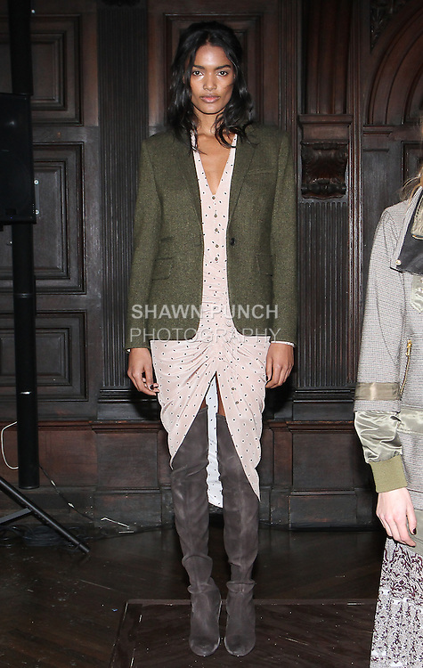 """Model Nadia poses in a dusty rose deco dot crepe de Chine v-neck button down blouse, dusty rose deco dot ruched drawstring hourglass skirt, and army green wood herringbone classic dickey blazer, from the Veronica Beard Fall 2016 """"Gypsy Caravan"""" collection presentation, at the Highline Hotel on February 15 2016, during New York Fashion Week Fall 2016."""