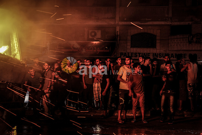 Palestinians look as firefighters try to extinguish fire from  soap factory that caught fire moments after it was hit by an Israeli airstrike in Gaza City August 10, 2014. Palestinian and Israeli negotiators on Sunday said they had accepted an Egyptian proposal for a new 72-hour truce with Israel, clearing the way for a possible resumption of talks on a long-term cease-fire arrangement in the Gaza Strip. Photo by Ezz Zanoun