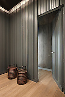 A minimal entrance hall with grey corrugated wall covering and wooden floor. Two wicker baskets stand in the corner.