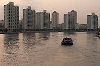 Daytime landscape view of residential building construction on a river in Shanghai, China.  © LAN