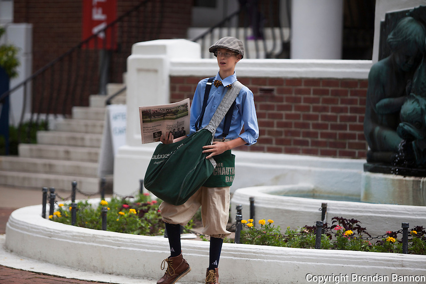 Noah sells newspapers in Bestor Plaza. During the summer season  the Chautauquan Daily publishes a newspaper  of local news and features for the residents and guests. Chautauqua, NY. June 27, 2014. Photo by Brendan Bannon