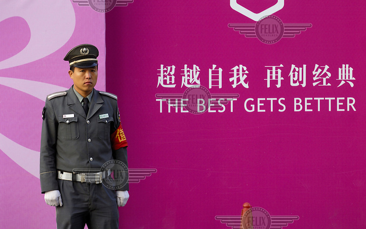 A construction site security guard in front of a typically vacuous advertising slogan for a new luxury shopping mall - 'The Best Gets Better'.