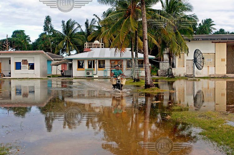 A man on a motorbike negotiates floodwaters outside the meteorological office on his return from feeding his animals.  The coral atoll is to vulnerable to sea level rise, particularly at high spring tides, when salty water seeps up through the ground and causes flooding...