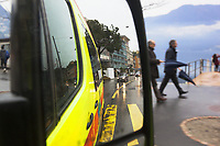 Switzerland. Canton Ticino. Lugano. View through a side mirror on an ambulance ride during a medical emergency intervention. The ambulance belongs to the Croce Verde Lugano. Mirror reflection. Tourists walk on the sidewalk near the lake. The Croce Verde Lugano is a private organization which ensure health safety by addressing different emergencies services and rescue services. Lake Lugano (or Lake Ceresio ) is a glacial lake. 27.01.2018 © 2018 Didier Ruef