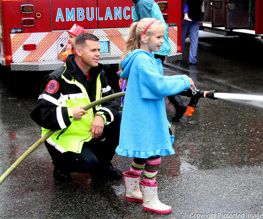 Holbrook Fireman John Howland shows his daughter Lauren Howland how to use a fire hose during the Holbrook Fire Department open house on Saturday, Oct. 11, 2014.<br /> (Photo by Gary Wilcox)