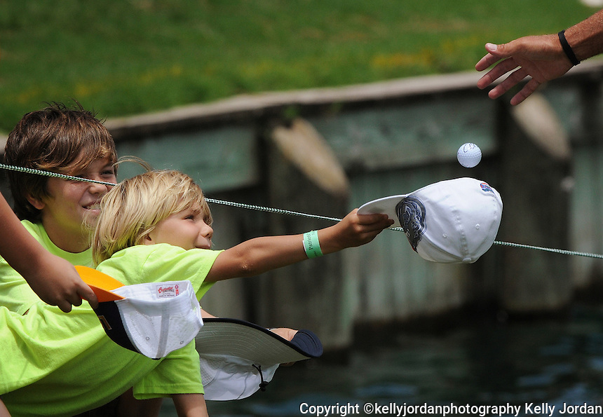Kelly.Jordan@jacksonville.com--051212--Tyler Connelly, 7, of Cape Coral holds out his hat to catch a golf ball from Robert Allenby as he leaves the 17th green during The Players Championship at TPC Sawgrass Saturday May 12, 2012 in Ponte Vedra Beach, Florida.(The Florida Times-Union, Kelly Jordan)