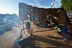 Seven-year old Abu Nyal cooks over a fire in a camp for more than 5,000 internally displaced persons in an Episcopal Church compound in Wau, South Sudan. Most of the families here were displaced by violence early in 2017, after a larger number took refuge in other church sites when widespread armed conflict engulfed Wau in June 2016.<br /> <br /> Norwegian Church Aid, a member of the ACT Alliance, has provided relief supplies to the displaced in Wau, and has supported the South Sudan Council of Churches as it has struggled to mediate the conflict in Wau. <br /> <br /> Parental consent obtained.