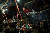 Steven passes over the audience during his trapeze act at the Sombrillita Circus. Around a dozen small circuses wander the poorer neighbourhoods near and around the city of Medellin putting on performances in what can be a hand to mouth existence. Despite falling audience numbers, new health and safety regulations and other bureaucracy these small family businesses, many of whom have existed for generations, still scrape a living in a world where the people are more accustomed to being entertained by soap operas than by live entertainment.