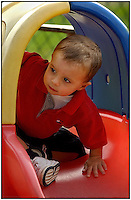 A toddler peers out from a large plastic toy car. Model released.