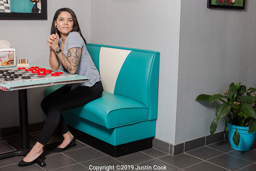 """A portrait of Brittany Atkinson, Office Manager at Hwy 55 Burgers in Mount Olive, NC Tuesday, January 8, 2019 (Justin Cook for The Wall Street Journal)<br /> <br /> Story Summary: JOBCLIMB by Chip Cutter. In this hot job market, many people have found it a good time to ask for raises, switch careers or get promoted. We talk to several people, representing a cross-section of careers, who have parlayed employers' needs for qualified talent into better jobs for themselves, advancing up the corporate ladder and earning more with every new role. Art: Brittany Atkinson cell: (919) 920-1526. Part of her story: Ms. Atkinson, 29, got hired in November as the office manager at the corporate headquarters for Hwy 55 Burgers, Shakes & Fries, a 1,500-employee restaurant franchise based in Mt. Olive, N.C. after 15 years waiting tables at Ruby Tuesdays and Buffalo Wild Wings. She has been told repeatedly by customers that she would never get an office job with better pay, benefits and weekends off because of her looks - covered in tattoos. In the tight job market, """"it's so much easier to kind of weasel your way in and get your foot in the door than it has been in the past,"""" she said. """"I don't think years ago I would have been able to find this job the way I had."""""""