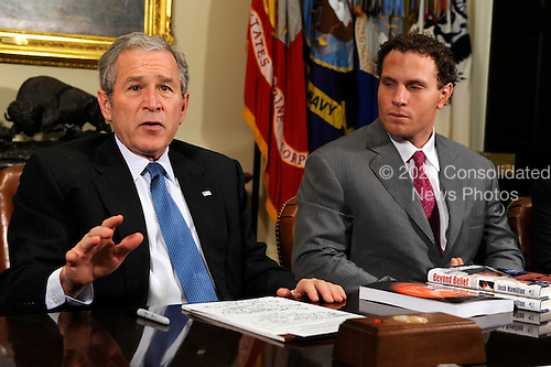 U.S. President George W. Bush (L) makes remarks to the press about progress in his administration's efforts in fighting drug abuse during a Meeting on Drug Use Reduction, at the White House, 11 December 2008, in Washington.  Major League Baseball player Josh Hamilton of the Texas Rangers (R), who battled drug abuse early in his career, but kicked the habit to become an All-Star, listens to remarks.