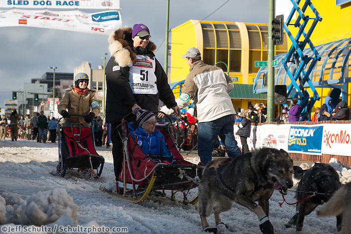 Philip Walters and team leave the ceremonial start line with an Iditarider at 4th Avenue and D street in downtown Anchorage, Alaska during the 2015 Iditarod race. Photo by Jim Kohl/IditarodPhotos.com
