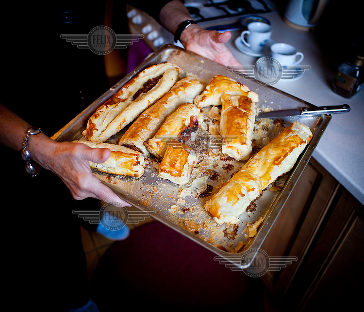 Wika Szmyt, a 74 year old DJ, holds a baking tray of pastries that she has just cooked in her apartment.