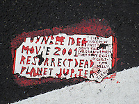 A Toynbee Tile is seen embedded into the pavement at a site in the Chelsea neighborhood of New York on Thursday, September 25, 2014. Toynbee tiles are messages of unknown origin embedded in streets in about two dozen major cities in the United States and four South American capitals. Since the 1980s, several hundred tiles have been discovered. (© Richard B. Levine)