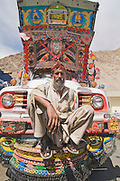 A Pakistani man sitting on the bumper of his truck in Pakistan