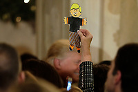 A guest holds up a paper cutout as United States President Donald J. Trump greets the audience at the Congressional Ball at White House in Washington on December 15, 2018. <br /> Credit: Yuri Gripas / Pool via CNP / MediaPunch