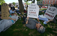 NWA Democrat-Gazette/BEN GOFF @NWABENGOFF<br /> Laura Villegas (from left), of Springdale, Janet Meyer of Fayetteville and Carol Riggs of Fayetteville lay down with tombstone-shaped signs Sunday, May 7, 2017, during a 'Die-In for ACA' hosted by Ozark Indivisible on the Bentonville square. The group marched around the square and lay down in a 'die-in,' with many holding tombstone-shaped signs carrying personal messages about how healthcare costs and losing coverage for pre-existing conditions could lead to their premature death. The event comes after the U.S. House of Representatives approved legislation Thursday to largely repeal and replace the Affordable Care Act.