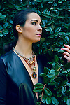 Woman with black hair in foliage staring out into space while wearing leather and necklace