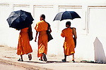 Three young monks take a walk, shaded by umbrellas.