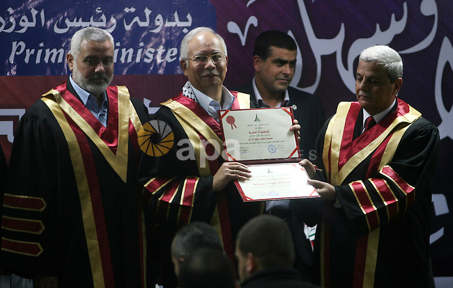 Malaysian Prime Minister Najib Razak (C) stands next to Palestinian  prime minister Ismail Haniya (L) as he receives an honourary doctorate during a visit to the Al-Aqsa University in Khan Yunis in the southern Gaza Strip January 22, 2013. Razak pledged solidarity with the Palestinians on his first trip to Gaza, and backed reconciliation efforts between Hamas and Fatah. Photo by Eyad Al Baba