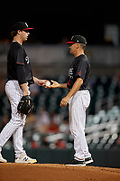 Birmingham Barons manager Omar Vizquel (13) takes the ball from pitcher John Parke (14) for a pitching change during a Southern League game against the Chattanooga Lookouts on July 24, 2019 at Regions Field in Birmingham, Alabama.  Chattanooga defeated Birmingham 9-1.  (Mike Janes/Four Seam Images)