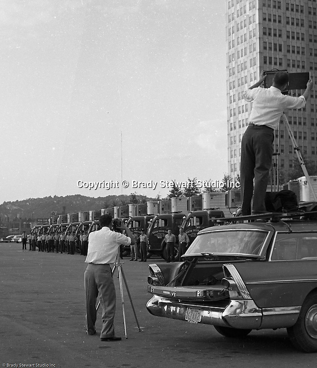 Pittsburgh PA:  Brady Stewart Studio on location for Morton Frozen Pies at Gateway Center in downtown Pittsburgh - 1957.  Assignment was for Ketchum McLeod and Grove Advertising. Brady Stewart Jr. and Ross Catanza handled the unique assignment.  View of Brady Stewart Jr. on top of the family's new 1957 Buick station wagon to get the right height for the shot and Ross Catanza shooting a 16mm film of the photo shoot
