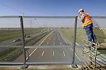WOERDEN - Boven de snelweg A12 bij Woerden plaatsen medewerkers van Heras drie meter hoge hekken op het viaduct. Met de in opdracht van Rijkswwaterstaat geplaatste hekken moet worden voorkomen dat voorbijgangers rotzooi of losliggend bouwmateriaal naar beneden op het verkeer gooien. Aanleiding voor het plaatsen van deze hekken die ondertussen ook op andere plaatsen zijn gemonteerd, is een dodelijk ongeval in 2005 waarbij een automobiliste overleed nadat haar auto was geraakt door een geworpen stoeptegel. COPYRIGHT TON BORSBOOM