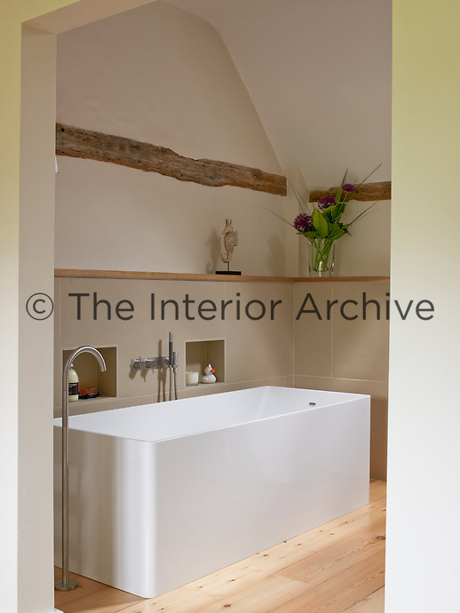 A box shaped bath in the bathroom of this converted manor house