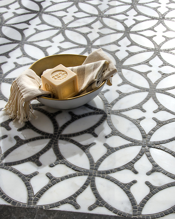 Omar, a hand-cut and waterjet stone mosaic, shown in polished Calacatta Tia and hand-chopped tumbled Cavern, is part of the Legend® Collection by New Ravenna.