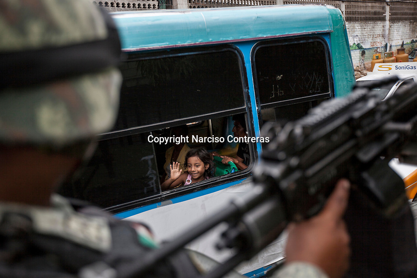"""June 17, 2018: A young girl waves to a military convoy passing by as army soldiers surveil """"Zapata"""" vicinity, a violence-plagued neighbourhood in Acapulco, Guerrero. A juncture of security forces, among them military, marines, federal police and local police joined under one-command to fight crime violence in the once-glamorous resort destination."""