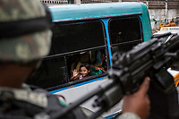 "June 17, 2018: A young girl waves to a military convoy passing by as army soldiers surveil ""Zapata"" vicinity, a violence-plagued neighbourhood in Acapulco, Guerrero. A juncture of security forces, among them military, marines, federal police and local police joined under one-command to fight crime violence in the once-glamorous resort destination."