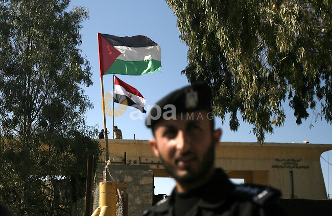 A Palestinian policeman stands in front of Rafah border crossing as Egyptian soldiers (top) keep watch next to the national flag on the Egyptian side, while Palestinian children (unseen) take part in a rally on the Palestinian side calling on Egyptian authorities to open the crossing in the southern Gaza Strip on January 29, 2014. Egypt occasionally permits people to enter and leave Gaza, but has refused to open on a permanent basis the only border crossing in the Hamas-run Palestinian coastal strip not controlled by Israel. Photo by Eyad Al Baba