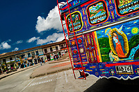 A colorfully painted, rustic bus, locally called 'escalera', is seen parked on the main plaza in Sonsón, a village in the coffee region (Zona cafetera) of Colombia, 15 October 2019.
