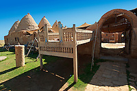 "Pictures of the beehive adobe buildings of Harran with a summer outdoor bed,  south west Anatolia, Turkey.  Harran was a major ancient city in Upper Mesopotamia whose site is near the modern village of Altınbaşak, Turkey, 24 miles (44 kilometers) southeast of Şanlıurfa. The location is in a district of Şanlıurfa Province that is also named ""Harran"". Harran is famous for its traditional 'beehive' adobe houses, constructed entirely without wood. The design of these makes them cool inside. 32"