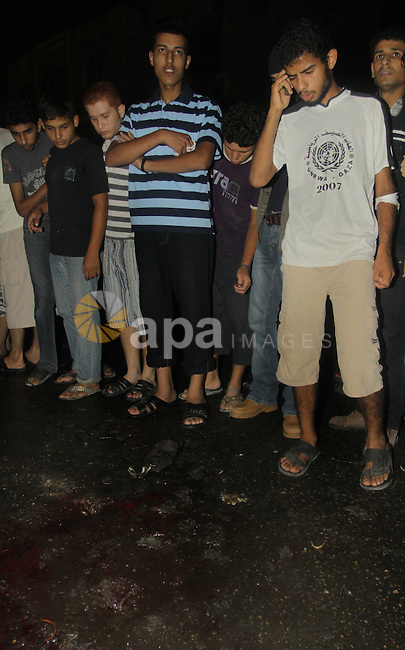 Palestinians inspect the Blood following an Israeli airstrike killing three Palestinian who were riding it, at the main road in Gaza City, Friday, Aug. 19, 2011. Palestinian official said that Dr. Monzer Qrakea, 35, and his brother Motaz, 23, and his son Islam, 5, were killed while they riding a motorcycle in Gaza city. Photo by Naaman Omar